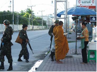 Des soldats contrôlant un moine. Photographe anonyme.