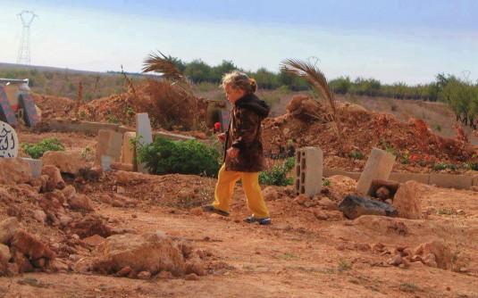 Une petite fille apporte une rose rouge au cimetière pour rendre hommage à son père décédé (c) Life for Syria