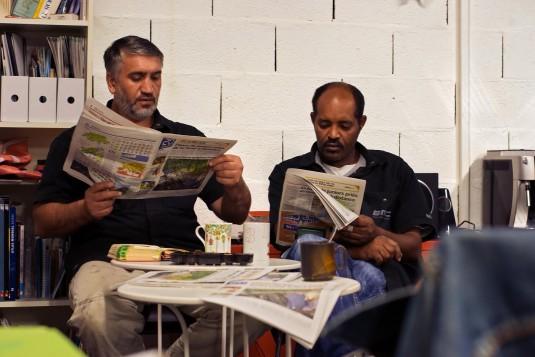 À la Maison du Vélo, Dzhamal commence la lecture quotidienne du journal qui a lieu dès 8h, pour habituer les migrants à la langue française. Son collègue Biniyam suit la lecture avec attention. © S.R. Torres
