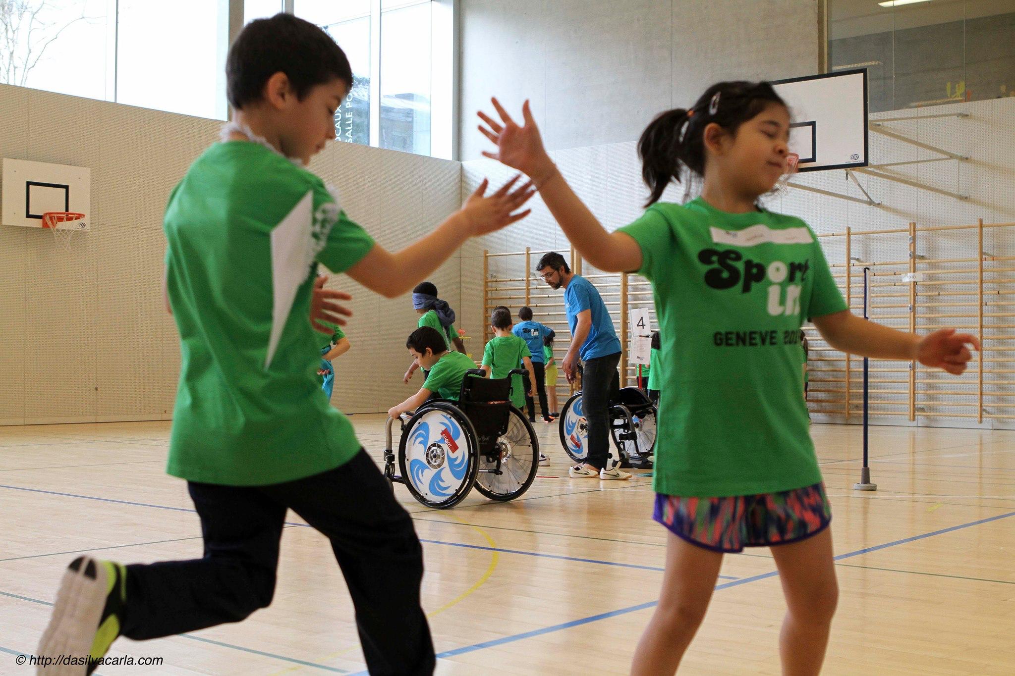 Concentration et engagement des élèves à chaque poste: estafette pieds/mains (au premier plan), poste sensibilisation au handicap avec estafette chaise roulante, yeux bandés et palmes (en arrière-plan). Photo de Carla da Silva - http://dasilvacarla.com/
