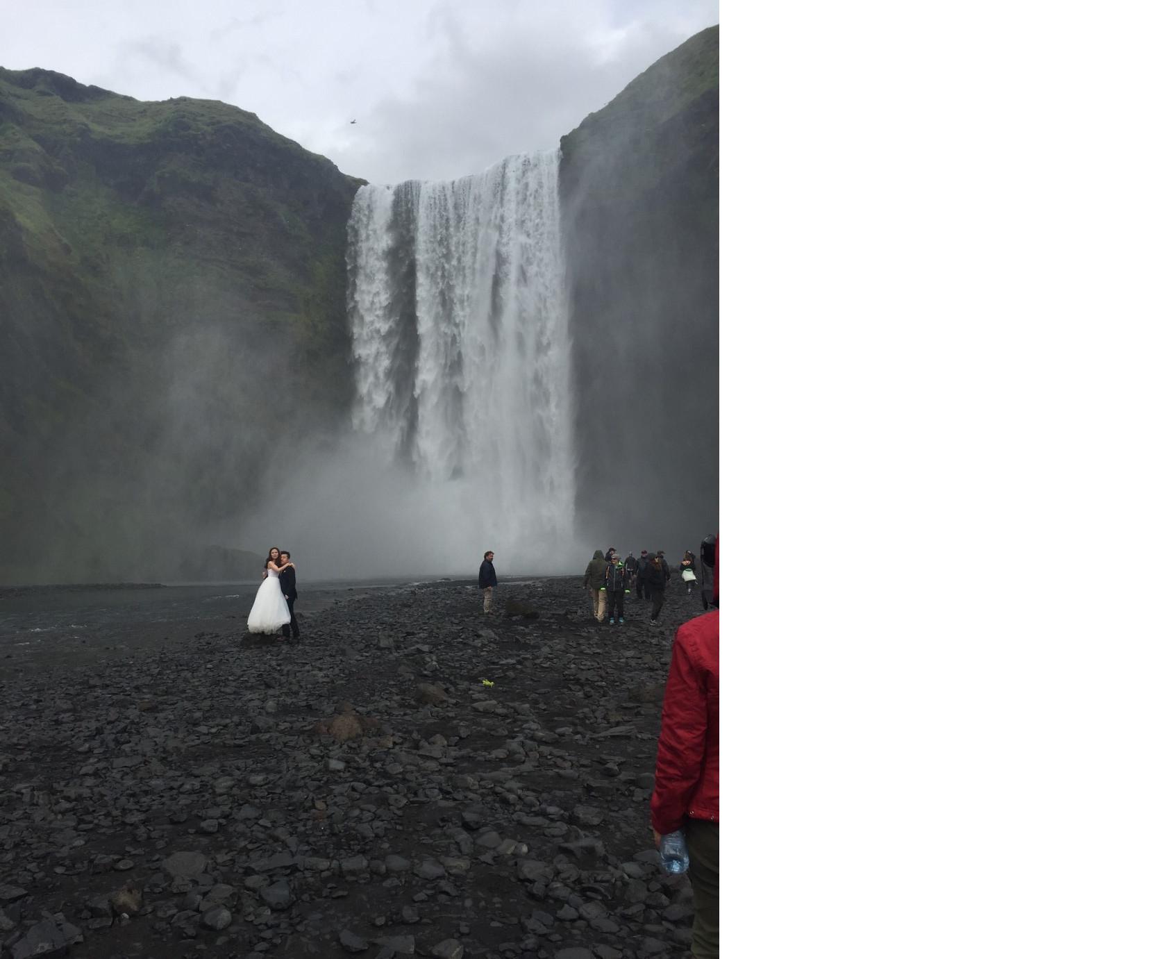 Un couple, apparemment marié depuis peu, fait un shooting photos devant la cascade de Skogafoss (Charlotte Frossard – 2017)